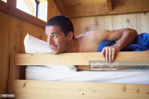 Young man waking up in bunk bed