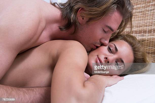 young man waking woman with a kiss - good morning kiss images stock photos and pictures