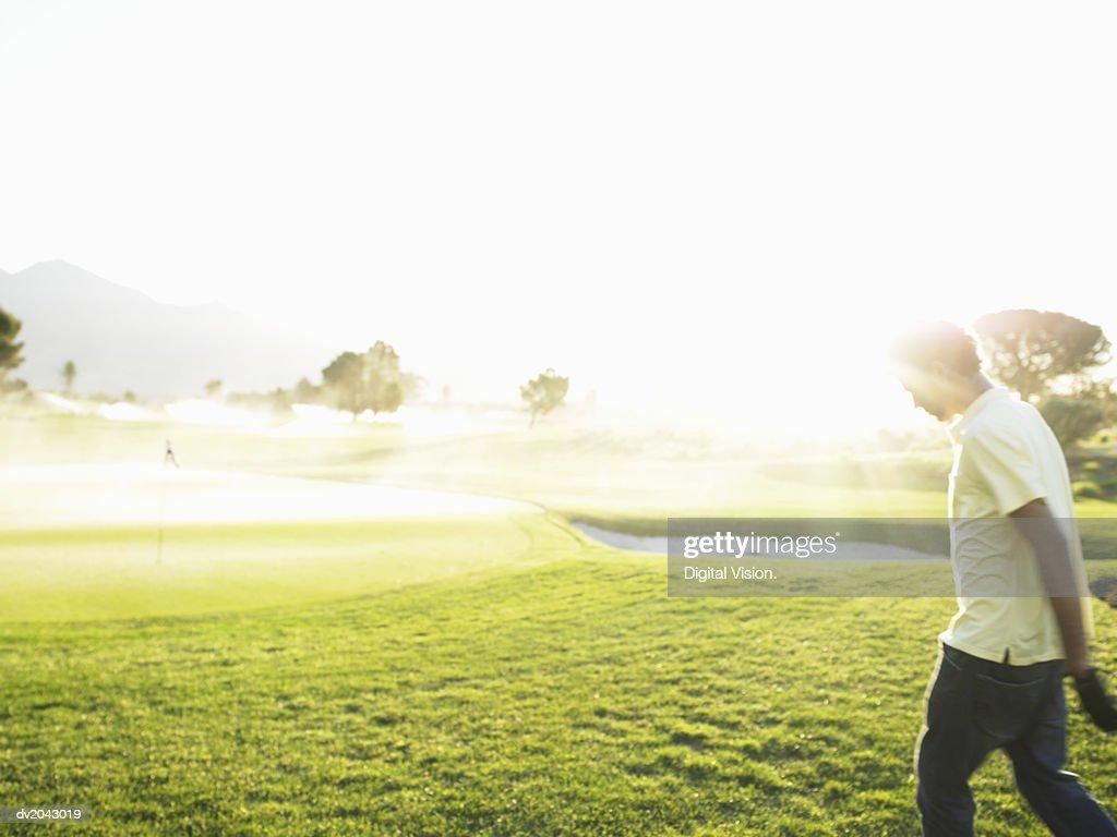 Young Man Walking Across a Golf Course : Stock Photo