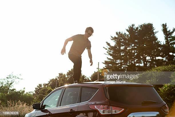 Young man walking across car roof