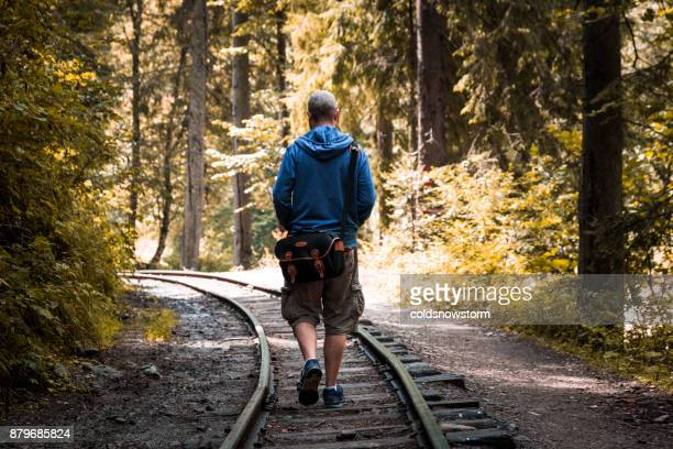 Young man walking alone on railway track in autumn forest