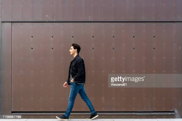 young man walking along a wall - seitenansicht stock-fotos und bilder