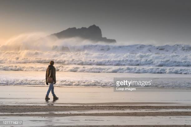 Young man walking along the shoreline looking out towards Goose Island off the coast of Newquay in Cornwall.