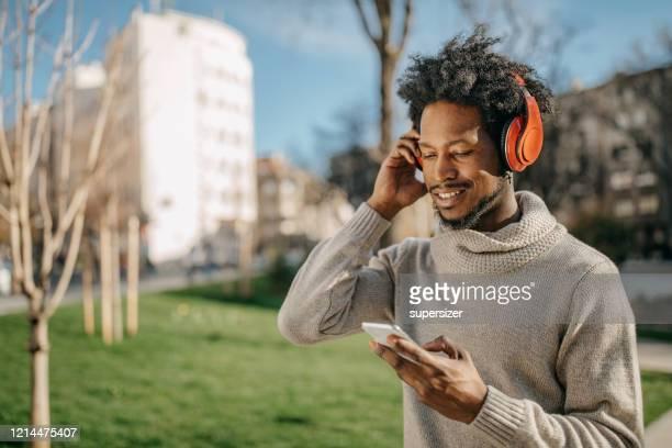 joven caminando y escuchando música - masculinidad moderna fotografías e imágenes de stock