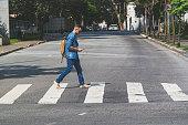Young man walking at crosswalk on a Sao Paulo's street