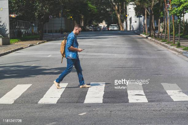 young man walking at crosswalk on a sao paulo's street - pedestrian stock pictures, royalty-free photos & images