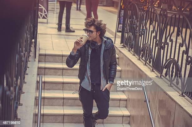Jovem homem a caminhar downstairs com uma Xícara de Café