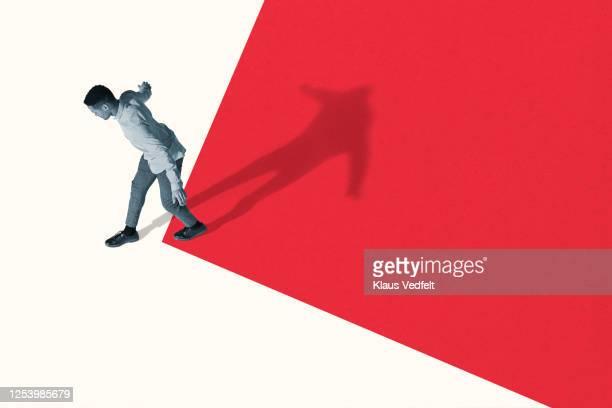 young man walking from red to white - zweifarbig farbe stock-fotos und bilder