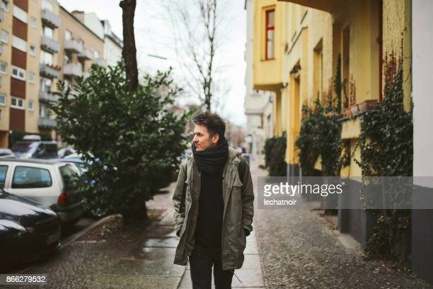 young man walking in berlin - parka coat stock photos and pictures