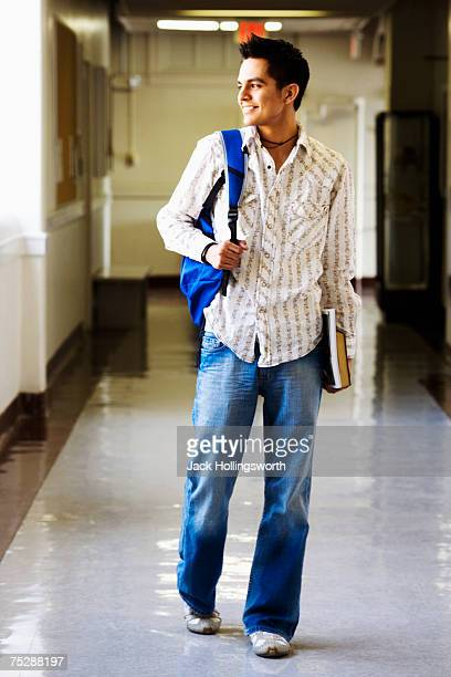 Young man walking in corridor, holding books