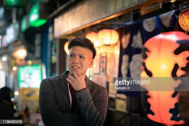 仕事の後、日本の居酒屋で歩く若い男 - のれん ストックフォトと画像