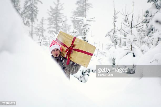Young man walking in snow, carrying gift