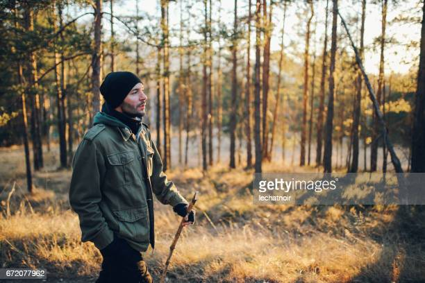 young man walking in the beautiful forest outdoors - parka coat stock photos and pictures