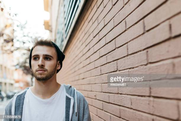 young man walking in the city next to a wall - tête composition photos et images de collection