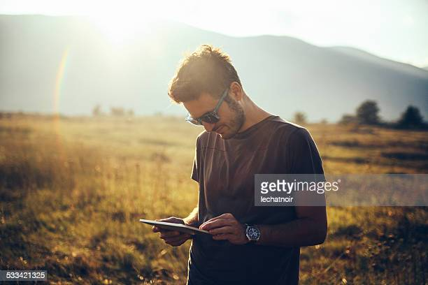 Young man walking in the nature, using a digital tablet