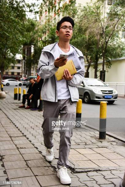 young man walking in urumqi, xinjiang - sergio amiti stock pictures, royalty-free photos & images