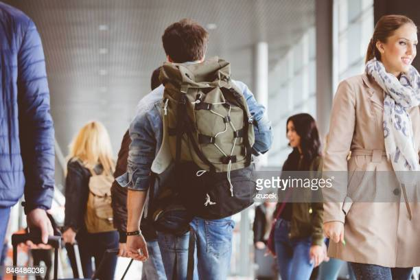 Young man walking inside crowded airport terminal