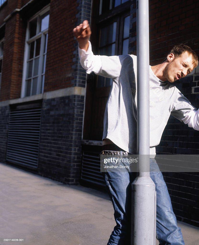 Young man walking into lamp post : Stock Photo