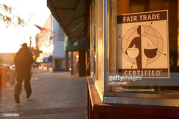 Young man walking into the setting sun past a restaurant that offers Fair Trade coffee on Main Street, Greenfield, Massachusetts, USA