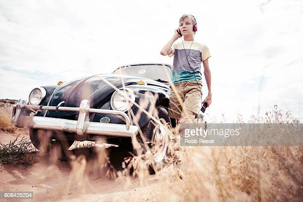 a young man walking next to a 1967 classic volkswagen beetle - robb reece stock pictures, royalty-free photos & images