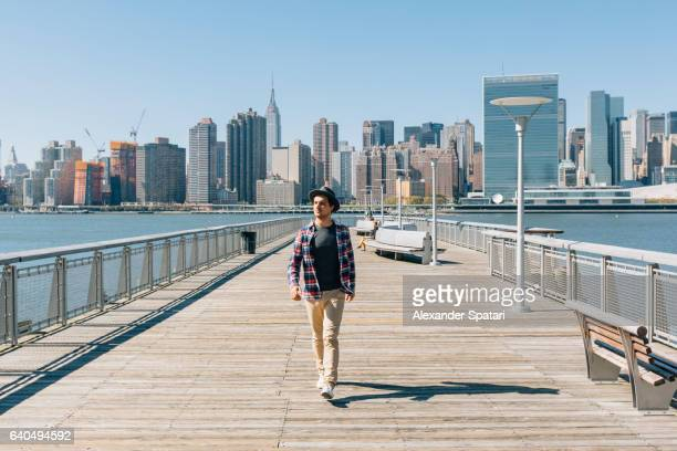 Young man walking on a pier with Manhattan skyline in the background, New York City, NY, USA