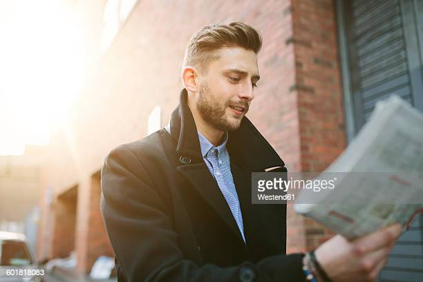 Young man walking on a street looking at newspaper