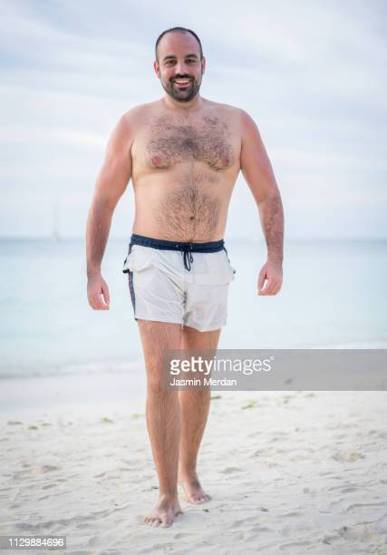 young man walking on beach - badkleding stockfoto's en -beelden
