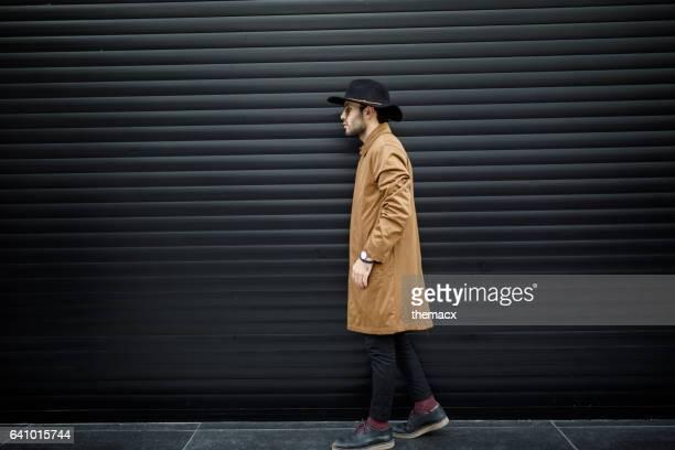 Jeune homme marchant sur fond noir stores