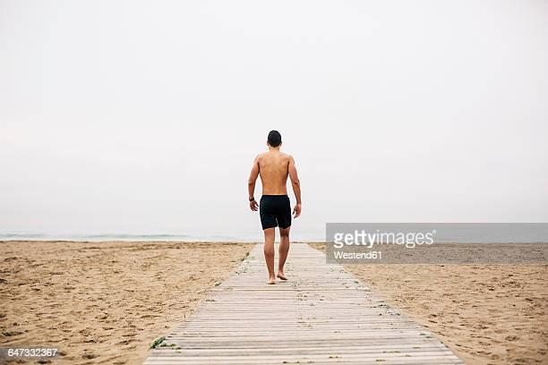 young man walking on boardwalk on the beach - hombre de espaldas playa fotografías e imágenes de stock