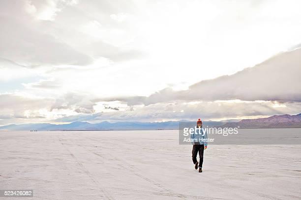 young man walking on bonneville salt flats at sunset, utah, usa - bonneville salt flats stock pictures, royalty-free photos & images