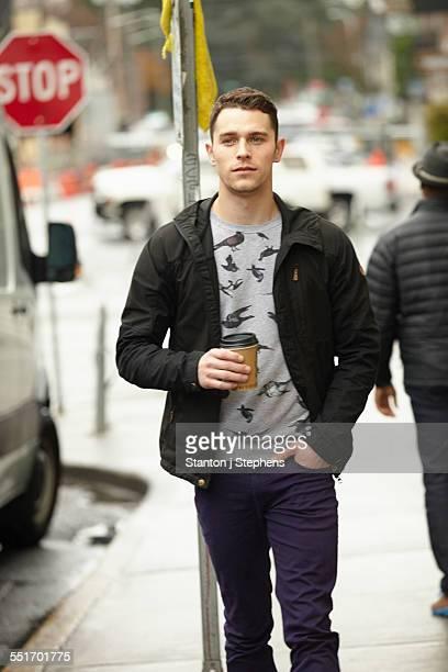 Young man walking on city sidewalk drinking takeaway coffee
