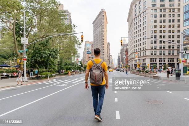 young man walking on fifth avenue towards flatiron building, rear view - op de rug gezien stockfoto's en -beelden