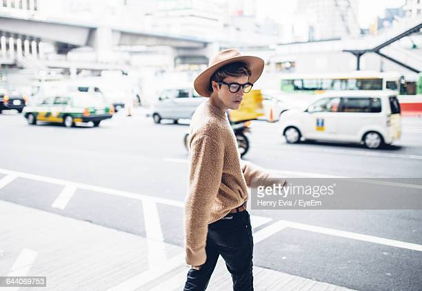Young Man Walking On Footpath In City