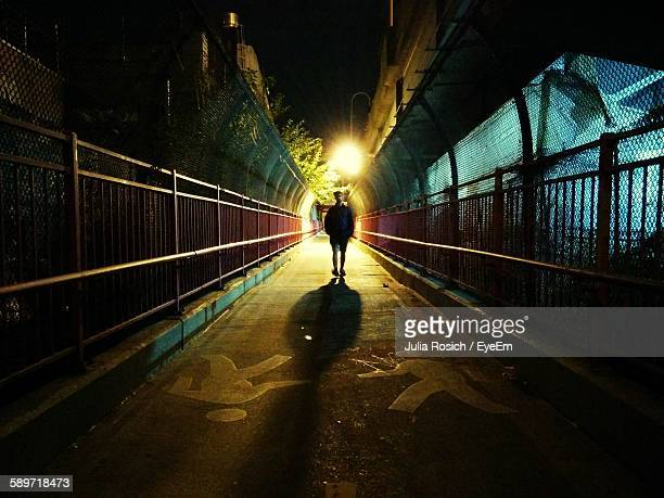 young man walking on illuminated pathway at night - mannelijke gelijkenis stockfoto's en -beelden