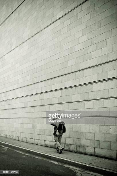 Young Man Walking on Sidewalk Against Concrete Block Wall