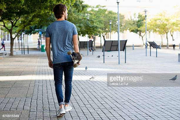 Young man walking on sidewalk with skateboard