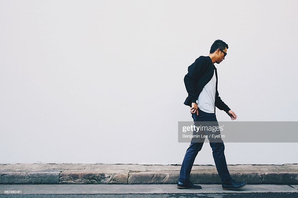 Young Man Walking On Street Against White Wall : Stock-Foto