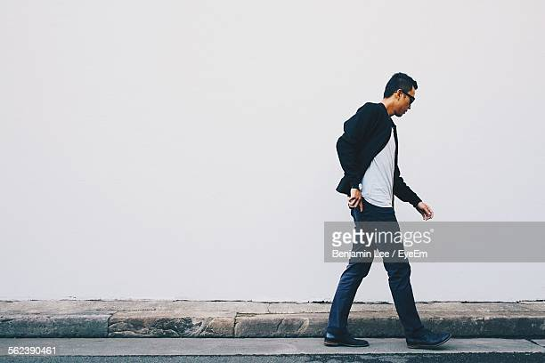 young man walking on street against white wall - van de zijkant stockfoto's en -beelden