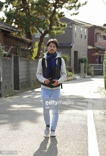 Young man walking on street with camera