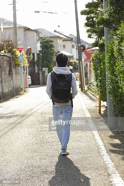 Young man walking on street,rear view