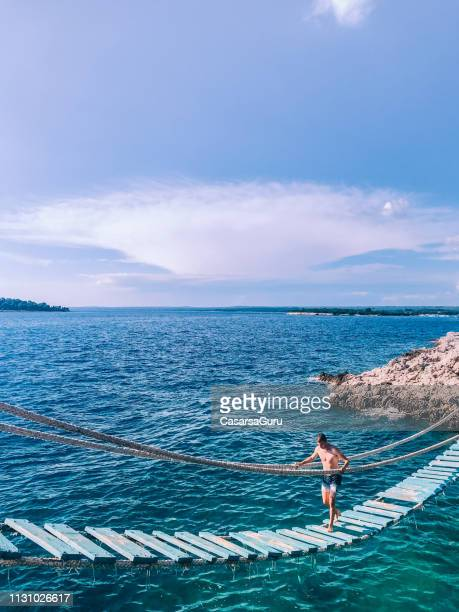 young man walking on suspension bridge over the sea - adriatic sea stock pictures, royalty-free photos & images