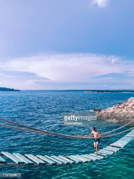 jonge man lopen op hangbrug over de zee - kroatië stockfoto's en -beelden