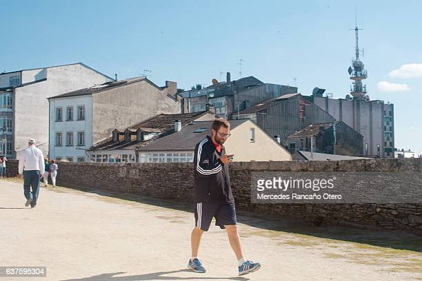 "Young man walking on the ""muralla"", Lugo, Spain."