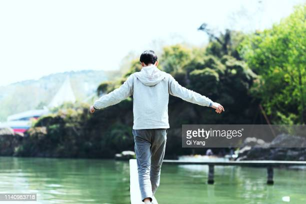 young man walking on the pier - wuhan stock photos and pictures