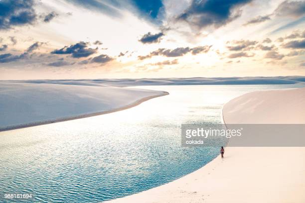 giovane che cammina sulle dune di sabbia di lençois maranhenses - parco nazionale foto e immagini stock