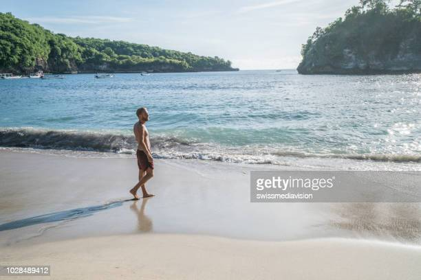 Young man walking on tropical beach in Bali enjoying beach holidays in tropical climate destination- people travel vacations beach concept