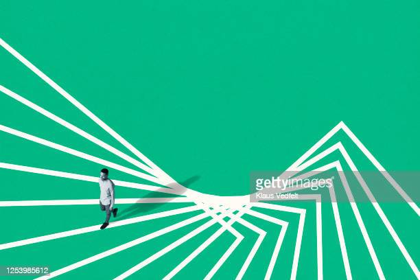young man walking on white abstract pattern - oresund region stock pictures, royalty-free photos & images