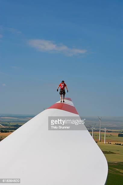 Young man walking on wind turbine wing