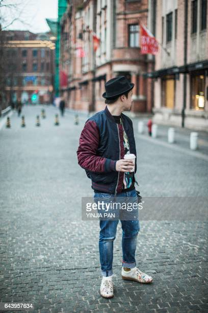 Young man walking outdoors, carrying coffee cup and gloves