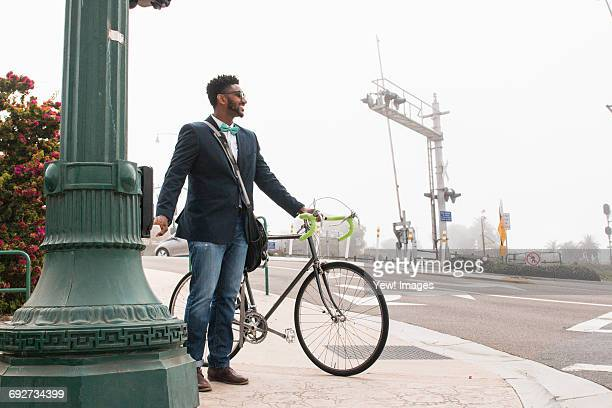 young man walking outdoors with bicycle - crossbody bag photos et images de collection